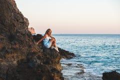 Junger blonder Frauentourist im blauen Kleid-sittig auf Felsen und Betrachten des Meeres Alanya, Mittelmeerregion, die Türkei Stockbild