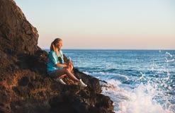 Junger blonder Frauentourist mit Glasflasche Limonade sittig auf Felsen durch das Meer bei Sonnenuntergang Alanya, Mittelmeer Lizenzfreies Stockbild
