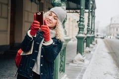 Junger blonder gelockter weiblicher Tourist in der warmen Kleidung lizenzfreie stockfotografie