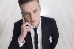 Junger blonder Geschäftsmann mit einem smartpone Lizenzfreie Stockfotografie
