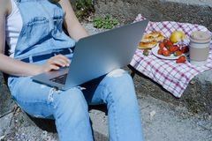 Junger blonder Hippie-Frauenfreiberufler in der Sonnenbrille, die an L arbeitet Stockbild