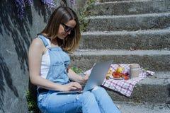 Junger blonder Hippie-Frauenfreiberufler in der Sonnenbrille, die an L arbeitet Stockfotos