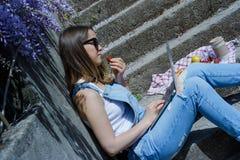 Junger blonder Hippie-Frauenfreiberufler in der Sonnenbrille, die an L arbeitet Lizenzfreie Stockfotos