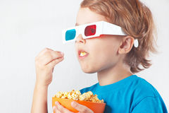 Junger blonder Junge in den Gläsern 3D Popcorn essend Stockfotos