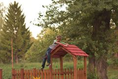 Junger blonder Junge, der auf dem roten Dachspitzen-Spielplatzhaus sich lehnt Stockfotos