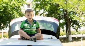 Junger blonder Junge, der auf der Dachspitze eines Autos sitzt Stockbild