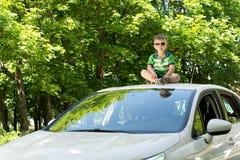 Junger blonder Junge, der auf die Oberseite eines Autos sitzt Lizenzfreies Stockbild