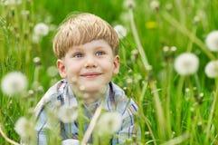 Junger blonder Junge, der auf einer Wiese sitzt Lizenzfreies Stockbild