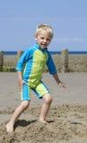 Junger blonder Junge, der auf Sand spielt Lizenzfreie Stockfotos