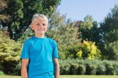 Junger blonder Junge, der an der Kamera lächelt Lizenzfreies Stockbild