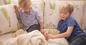 Junger blonder Junge, der die Füße seines Bruders auf einem Sofa kitzelt Stockfotos