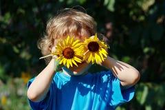 Junger blonder Junge, der draußen mit Sonnenblumen spielt Stockfotos