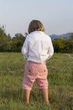 Junger blonder Junge, der draußen pinkelt stockbilder