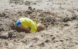 Junger blonder Junge, der ein Loch gräbt Lizenzfreies Stockbild