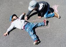 Junger blonder Junge, der einen Kreideentwurf eines jungen Mädchens auf der Straße zeichnet Lizenzfreie Stockfotografie