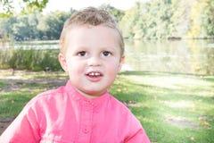 Junger blonder Junge, der im Park nahe See im Sommer lächelt Lizenzfreie Stockbilder