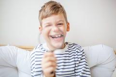 Junger blonder Junge, der Lupe hält und an der Kamera lächelt Lizenzfreie Stockbilder