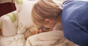 Junger blonder Junge, der mit seinem Babybruder spielt Lizenzfreie Stockfotos