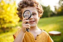 Junger blonder Junge, der mit Vergrößerungsglas spielt Stockfotografie
