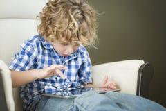 Junger blonder Junge, der sein Computer-Tablet verwendet Stockfotografie