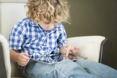 Junger blonder Junge, der sein Computer-Tablet verwendet Lizenzfreie Stockbilder