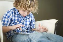 Junger blonder Junge, der sein Computer-Tablet verwendet Lizenzfreies Stockbild