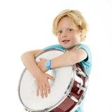 Junger blonder Junge, der Trommel hält Stockfotos