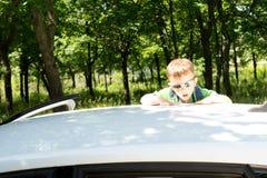 Junger blonder Junge, der zur Dachspitze eines Autos klettert Stockbilder