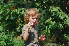 Junger blonder Junge, durchbrennend Luftblasen an einem sonnigen Tag Stockbild