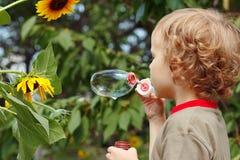 Junger blonder Junge, durchbrennend Luftblasen an einem sonnigen Tag Stockbilder