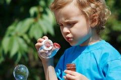 Junger blonder Junge, durchbrennend Luftblasen an einem sonnigen Tag Stockfotografie
