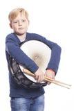 Junger blonder Junge hält Trommel gegen weißen Hintergrund Stockfoto