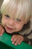 Junger blonder Junge haftet Jobstepp-Strichleiter an stockbilder