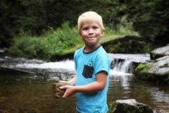 Junger blonder Junge halten Stein durch den Fluss Stockfotos