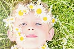 Junger blonder Junge mit Daisy Crown Lizenzfreie Stockbilder
