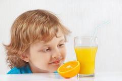 Junger blonder Junge mit einem Glas des frischen Safts und der Orange Stockbilder