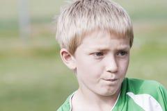 Junger blonder Junge mit nachdenklichem Ausdruck Stockbilder