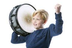 Junger blonder Junge mit Trommel gegen weißen Hintergrund zeigt Muskel Lizenzfreies Stockfoto