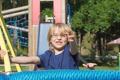 Junger blonder Junge spielt an den Kletterstangen. Stockbilder