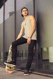 Junger blonder Kerl auf Skateboard in der zufälligen Ausstattung in der städtischen Verdichtereintrittslufttemperat Stockfoto