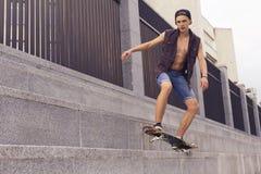Junger blonder Kerl auf Skateboard in der zufälligen Ausstattung in der städtischen Verdichtereintrittslufttemperat Stockbild