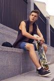 Junger blonder Kerl auf Skateboard in der zufälligen Ausstattung in der städtischen Verdichtereintrittslufttemperat Lizenzfreie Stockfotografie