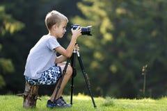Junger blonder Kinderjunge, der auf Baumstumpf auf der grasartigen Reinigung macht Foto mit Stativkamera sitzt stockfotos