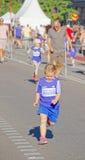 Junger blonder Mädchenbetrieb, andere Läufer hinten Lizenzfreies Stockbild