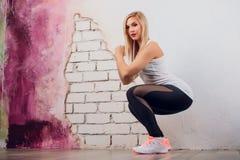 Junger blonder Mädchenfrauen-Eignungstrainer zeigt Übungshaltung Lizenzfreie Stockfotografie