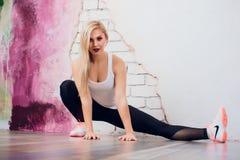 Junger blonder Mädchenfrauen-Eignungstrainer zeigt Übungshaltung Stockbild