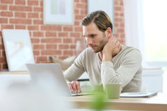 Junger blonder Mann auf Laptop zu Hause Lizenzfreies Stockbild