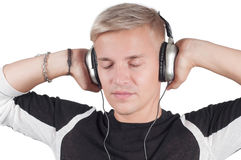 Junger blonder Mann in den Kopfhörern mit geschlossenen Augen Stockfoto