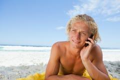 Junger blonder Mann, der auf dem Strand bei der Unterhaltung am Telefon liegt Stockbilder