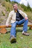 Junger blonder Mann, der auf hölzernem sitzt Stockbild